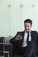 Executive looking at cell phone with concerned look