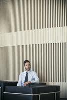 Businessman waiting in lobby 11001065635| 写真素材・ストックフォト・画像・イラスト素材|アマナイメージズ