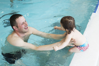Little girl learning to swim with help of parent