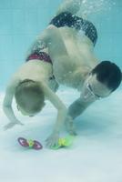 Father helping boy swim to bottom of pool to retrieve toy 11001065668| 写真素材・ストックフォト・画像・イラスト素材|アマナイメージズ