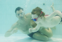 Father helping boy learn to swim underwater 11001065670| 写真素材・ストックフォト・画像・イラスト素材|アマナイメージズ