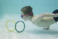 Boy retrieving rings from bottom of swimming pool 11001065671| 写真素材・ストックフォト・画像・イラスト素材|アマナイメージズ