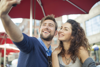 Couple posing for a selfie at an outdoor cafe