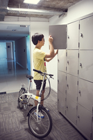 College student pausing by lockers with bicycle