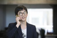 Man using cell phone, smiling cheerfully 11001065702| 写真素材・ストックフォト・画像・イラスト素材|アマナイメージズ
