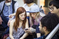 Young adult friends hanging out and using smartphone together 11001065771| 写真素材・ストックフォト・画像・イラスト素材|アマナイメージズ