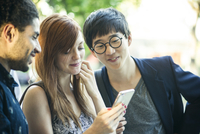 Young adult friends watching video on smartphone together 11001065778| 写真素材・ストックフォト・画像・イラスト素材|アマナイメージズ
