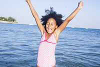 Girl in water raising arms with excitement