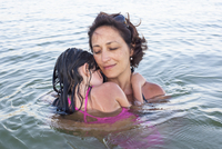 Mother and daugther wading in sea