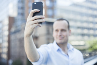Man using smartphone to take a selfie 11001065819| 写真素材・ストックフォト・画像・イラスト素材|アマナイメージズ
