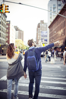 Couple crossing city street, rear view