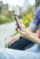 Couple using smartphone outdoors, cropped