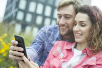 Couple using smartphone together outdoors