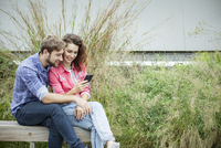 Couple sitting together on park bench, looking at smartphone