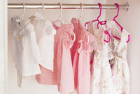 Baby clothes hanging in closet