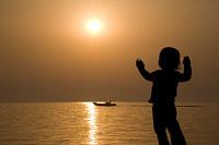 朝日と船を眺める子供のシルエット