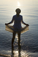スカートを上げる女性のシルエット