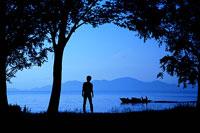 琵琶湖を眺める女性と舟のシルエット