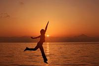 朝焼けとジャンプする女性のシルエット