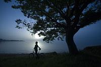 自転車を停めて眺める女性のシルエット