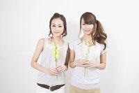 キンギョソウを持つ女性二人 11002053812| 写真素材・ストックフォト・画像・イラスト素材|アマナイメージズ