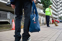掃除をする管理人の男性と向かいに立つ男子高生 11002053843| 写真素材・ストックフォト・画像・イラスト素材|アマナイメージズ