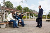 ベンチに座る四人の女性と挨拶を交わす中年ビジネスマン