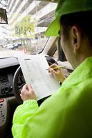 車内でチェックをする防犯パトロール中の男性