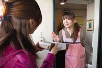 玄関口で御歳暮を渡そうとする女性と遠慮する女性 11002053898| 写真素材・ストックフォト・画像・イラスト素材|アマナイメージズ