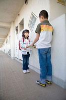 団地内の通路でファイルの受け渡しをする男の子と女の子 11002053900| 写真素材・ストックフォト・画像・イラスト素材|アマナイメージズ