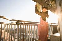 ベランダで洗濯物を干す女性 11002053903| 写真素材・ストックフォト・画像・イラスト素材|アマナイメージズ