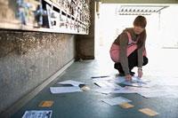 通路に落ちたチラシを拾う女性 11002053913| 写真素材・ストックフォト・画像・イラスト素材|アマナイメージズ