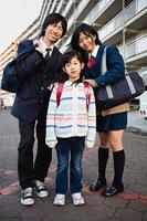 団地をバックにして立つ高校生カップルと女の子 11002053916| 写真素材・ストックフォト・画像・イラスト素材|アマナイメージズ