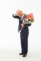 花束を持ち泣いている60代男性