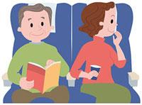 新幹線の座席で寛ぐ中高年夫婦