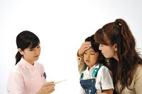 女の子の体温を測る看護師と母親