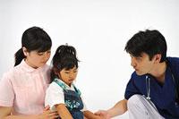 女の子を診察する医師と看護師