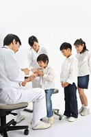 子供達に注射する医師と看護師