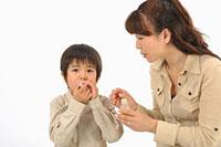 男の子に薬を飲ませる母親