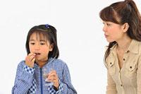 薬を飲む女の子と母親