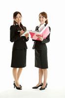 ファイルとノートを持つ二人女性