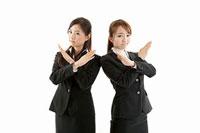 手でバツを作る二人の女性