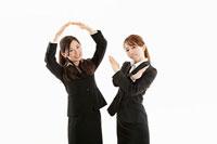 手でマルとバツを作る二人の女性