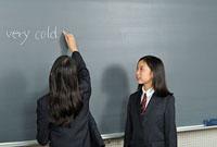 黒板に文字を書く女子高校生二人