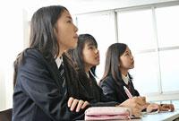 机に座る女子高校生三人