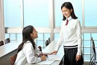 教室で談笑する女子高校生二人