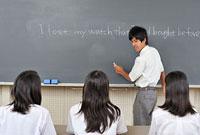 机に座る女子三人と黒板の前に立つ男子