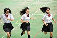 グラウンドを走る女子高校生三人
