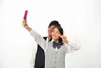 携帯電話で写真を撮る高校生二人