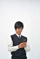 携帯電話を持つ男子高校生 11002056628| 写真素材・ストックフォト・画像・イラスト素材|アマナイメージズ